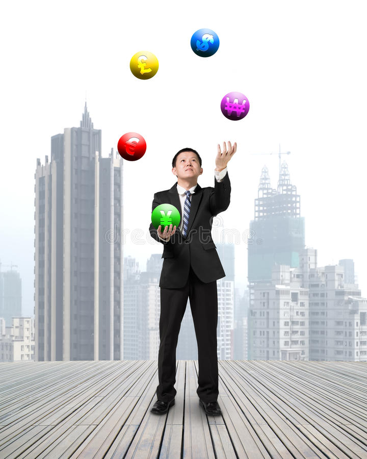 Businessman throwing and catching currency symbol balls stock image
