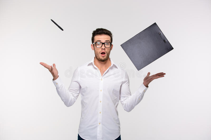 Businessman throwing clipboard and pen into the air royalty free stock image
