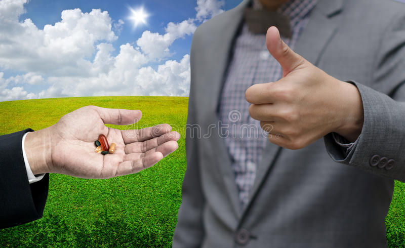 Businessman thumb up with drugs pills stock images
