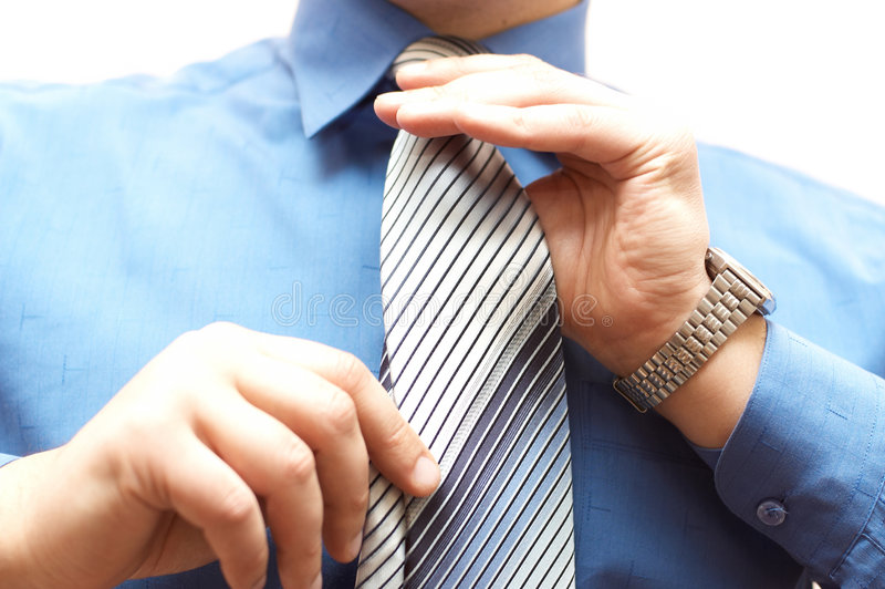 Businessman ties his neck tie stock photos