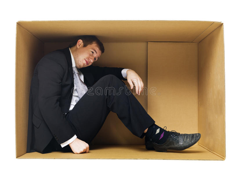 Businessman in a tight cardboard royalty free stock photography