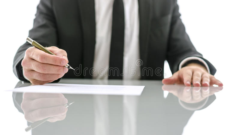Businessman about to sign important document. Business man sitting at white desk about to sign important document stock photos