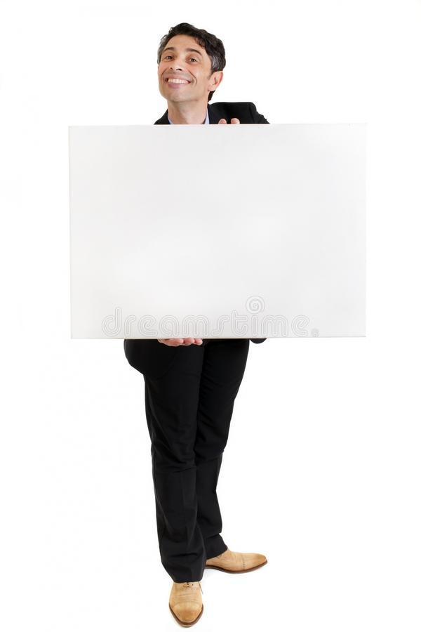 Businessman with a toothy grin with a blank sign. Businessman or salesman in a smart suit standing with a toothy ingratiating grin holding a blank sign in his royalty free stock image