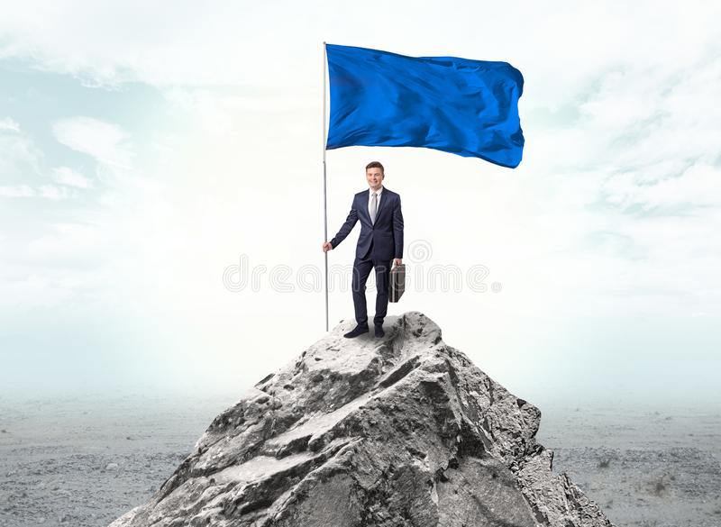 Businessman on the top of a the mountain holding flag stock photography