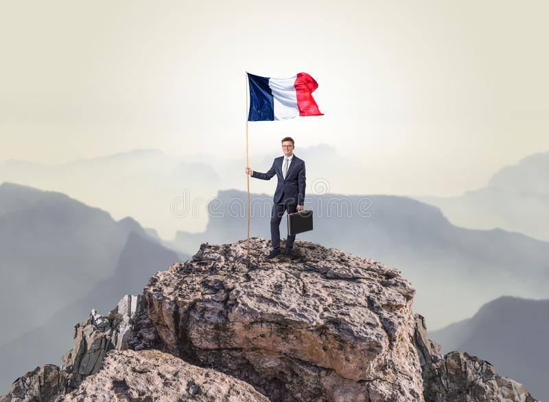 Businessman on the top of a rock holding flag royalty free stock photography