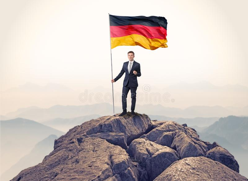 Businessman on the top of a rock holding flag stock photo