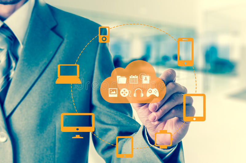 Businessman touching a cloud connected to many objects on a virtual screen, concept about internet of things.  stock images