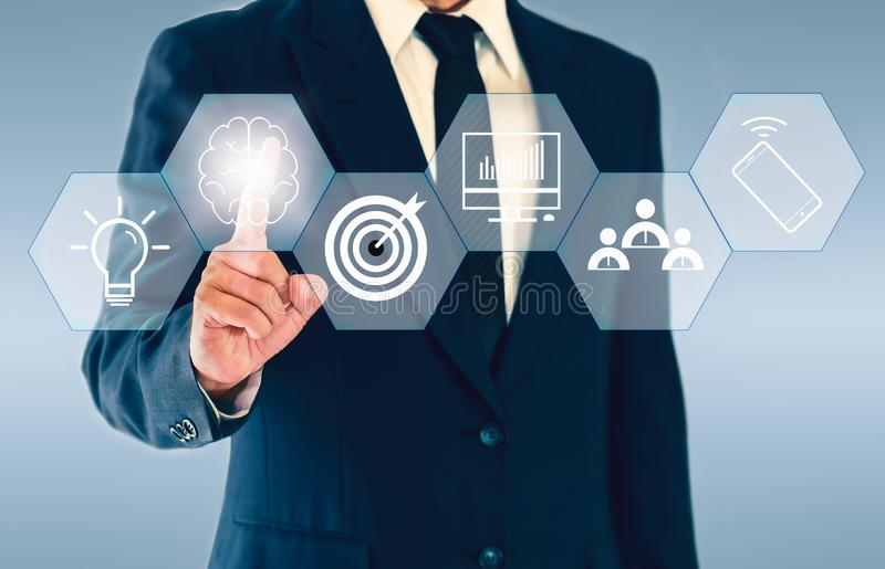 Businessman touching hexagonal button about brainstorming a concept such as teamwork, ideas, plan, and goal royalty free stock photography