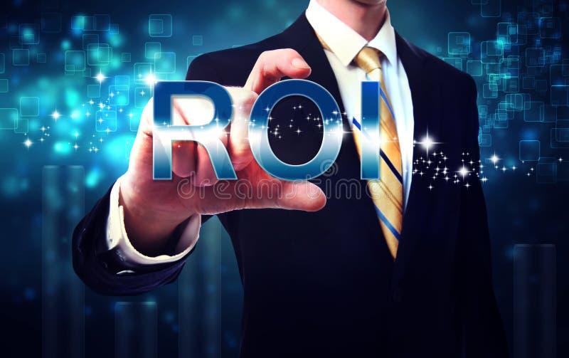 Businessman touching ROI (return on investment). On blue technology background stock photo
