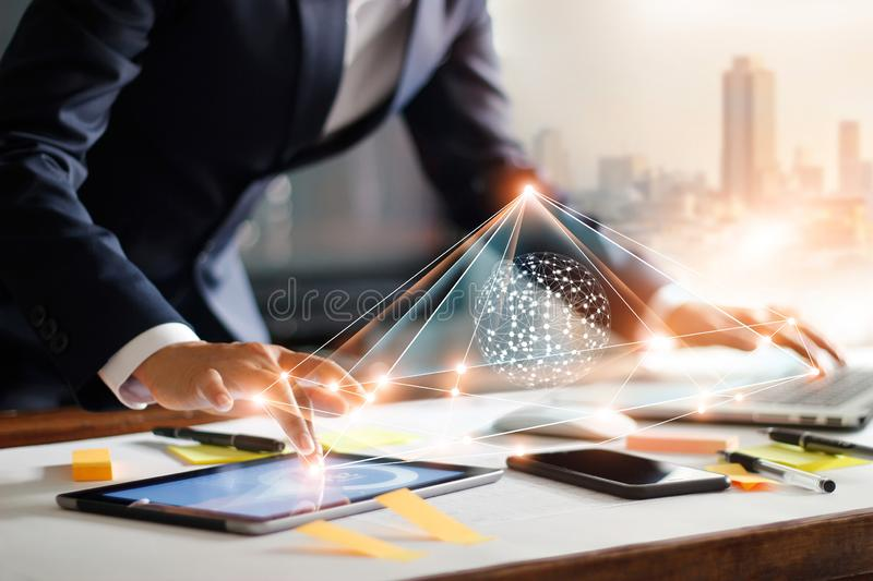 Businessman touching tablet and laptop. Managing data exchange. Businessman touching tablet and laptop. Management global structure networking and data exchanges stock photography