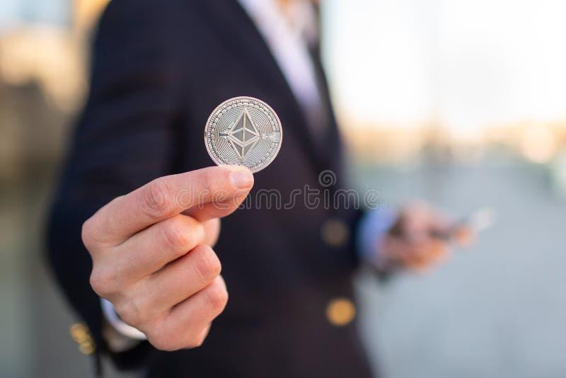 Businessman trader holding Ethereum cryptocurrency. stock image