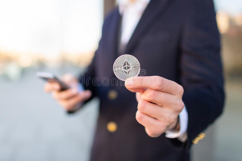Businessman trader holding Ethereum cryptocurrency. stock photography