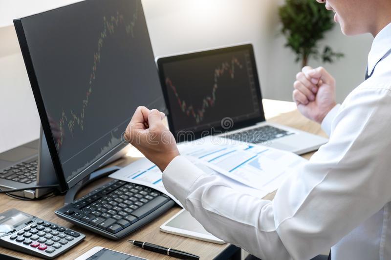 Businessman trading stocks online, stock broker looking at graph working and analyzing with display screen and happy to deal on a. Exchange, Stock exchange royalty free stock images