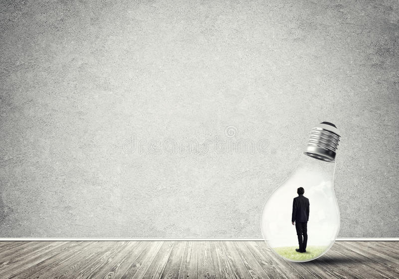 Businessman trapped in bulb. Businessman inside of light bulb in empty concrete room stock photos