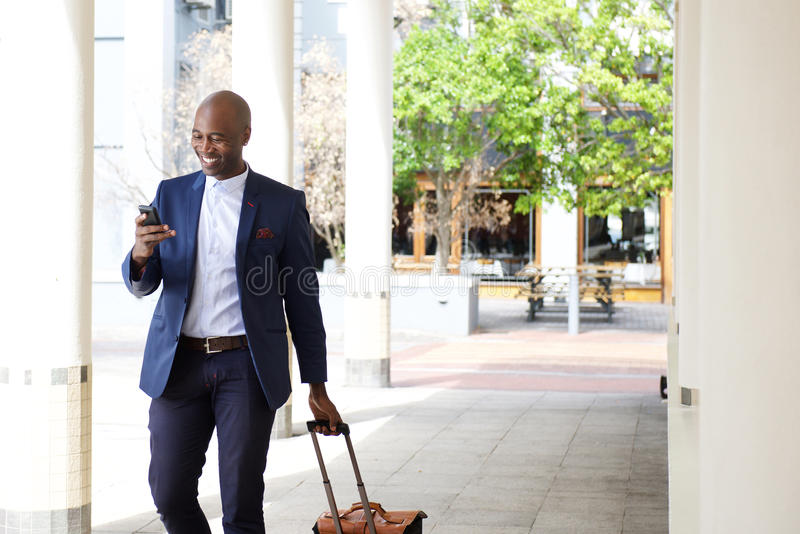 Businessman traveling with a bag and mobile phone royalty free stock image