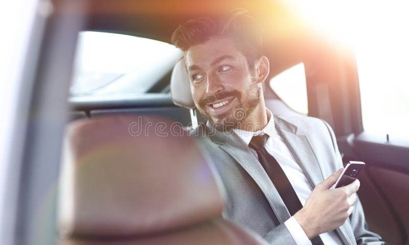 Unsmiling businessman sitting in the back seat in his car stock photo
