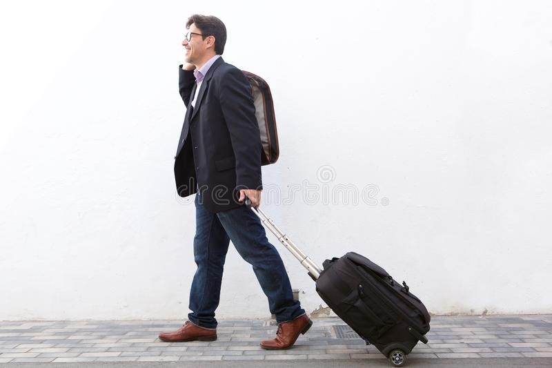 Businessman traveling with his suitcase and talking on cell phone outdoors royalty free stock image