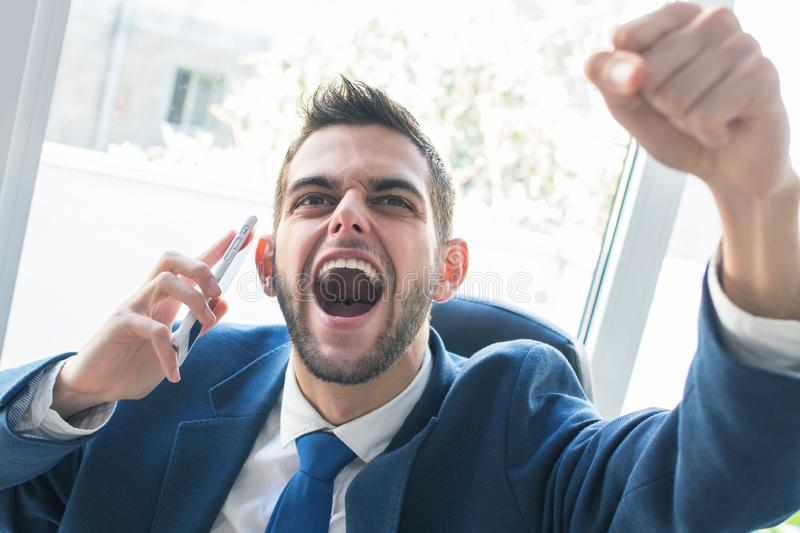 Businessman triumphant with phone royalty free stock photos
