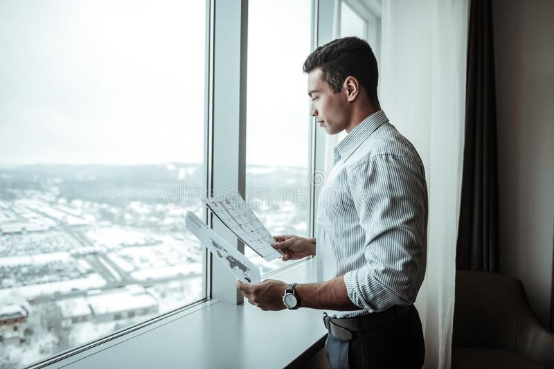 Businessman wearing trousers and shirt standing near window. Businessman in trousers. Businessman wearing dark trousers and striped shirt standing near window royalty free stock photos