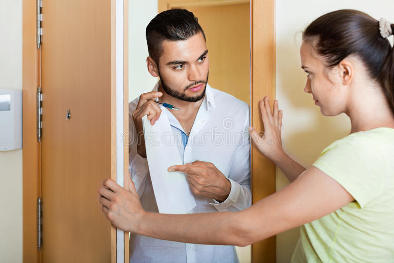 Businessman trying to collect money. Serious businessman trying to collect money from housewife at door royalty free stock photos