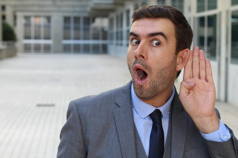Businessman trying to hear a gossip royalty free stock image