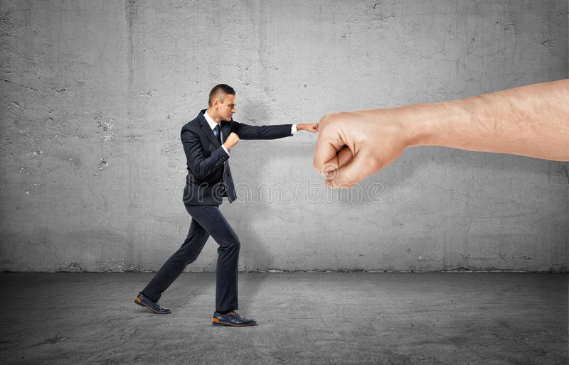 Businessman is trying to resist a huge male fist and move it away on the gray background stock photos