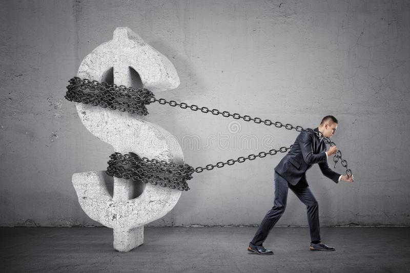 A businessman tugs at a chain trying to move a large concrete dollar sign from its place. stock image