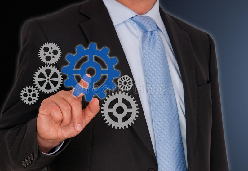 Businessman turning cogwheels on screen. Business, teamwork, performance, consulting, coaching or leadership concept image royalty free stock photo