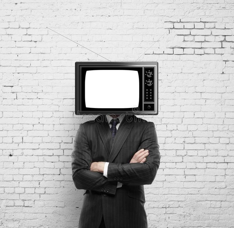 Man with tv head. Businessman with tv head on a brick wall background royalty free stock photo