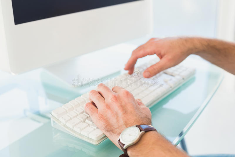 Businessman typing on computer keyboard. In his office stock photos