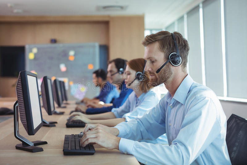 Businessman typing on keyboard at call center. Side view of businessman typing on keyboard at desk in call center royalty free stock photography