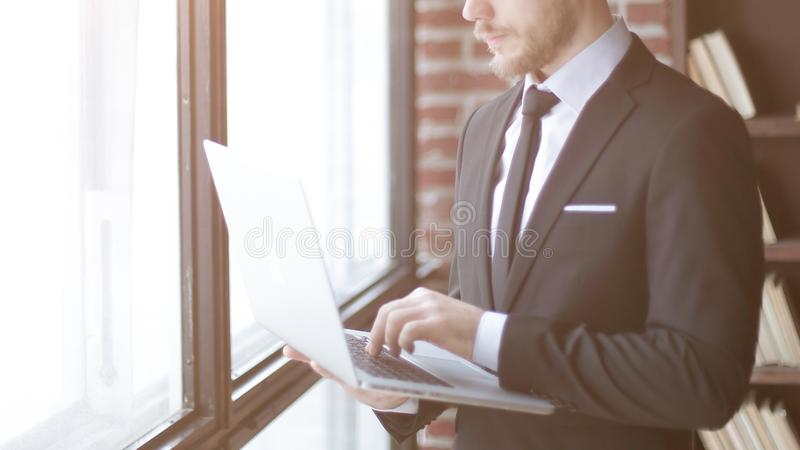Businessman typing on laptop while standing in office royalty free stock photography