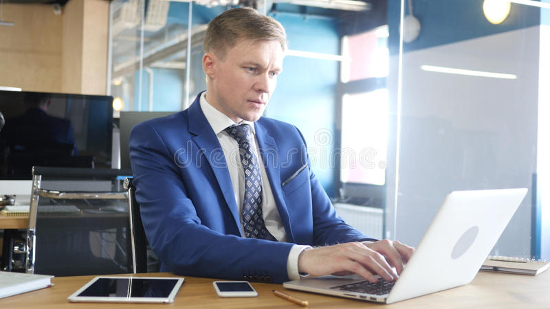 Businessman Typing on laptop at Work stock photo
