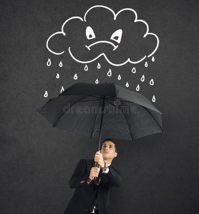 Businessman with umbrella and a angry cloud with rain. Concept of crisis and financial trouble stock photos