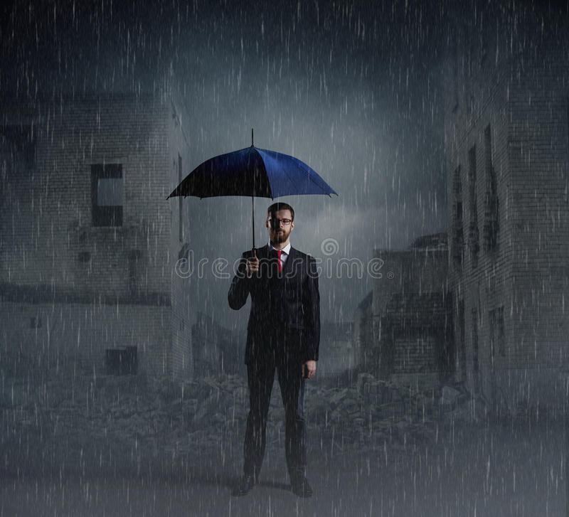 Businessman with umbrella standing over apocalyptic background. Crisis, default, setback concept. royalty free stock image