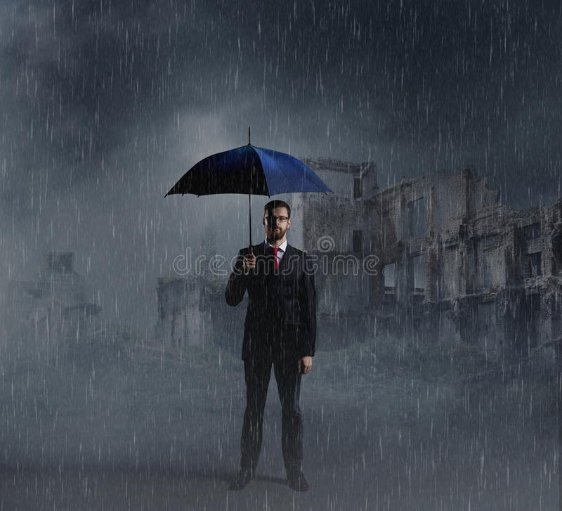 Businessman with umbrella standing over apocalyptic background. Crisis, default, setback concept. stock images