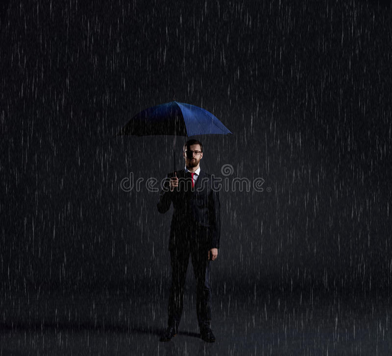 Businessman with umbrella standing under the rain. Dark, dramatic background. Business, failure, crisis, concept. royalty free stock photos