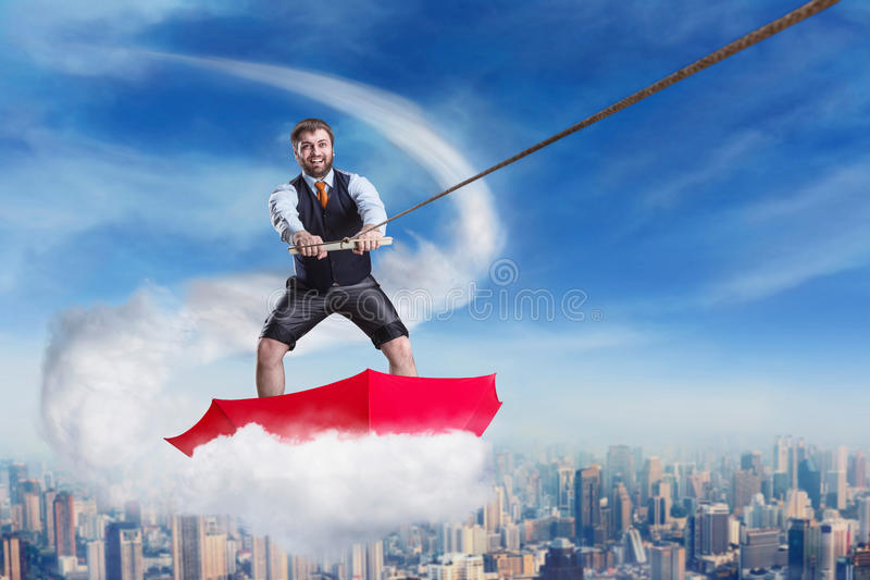 Businessman in umbrella on the cloud stock image