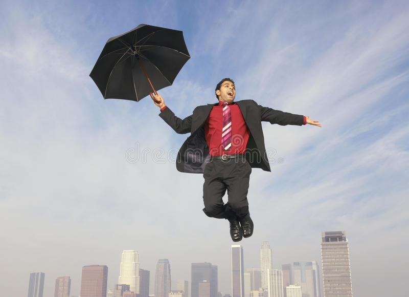 Download Businessman With An Umbrella In Midair Stock Photo - Image: 29649176