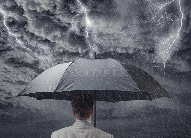 Businessman with umbrella sheltering from approaching storm stock photo