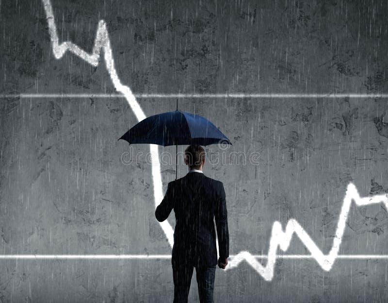 Businessman with umbrella standing over column diagram background. Business, crisis, default concept. stock photos