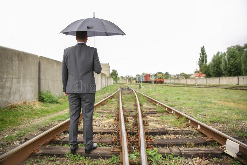 Businessman with umbrella standing railway track. Concept of choice stock photos