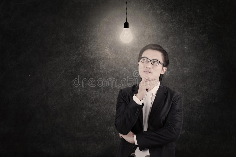 Businessman Under Lit Bulb Thinking Of Idea Royalty Free Stock Photos