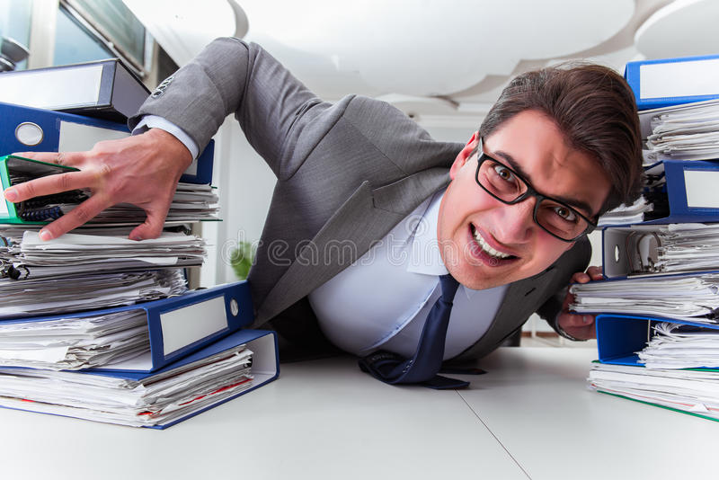The businessman under stress due to excessive work. Businessman under stress due to excessive work stock image