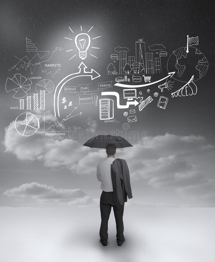 Businessman under an umbrella looking at drawings. Of charts and arrows royalty free stock photos