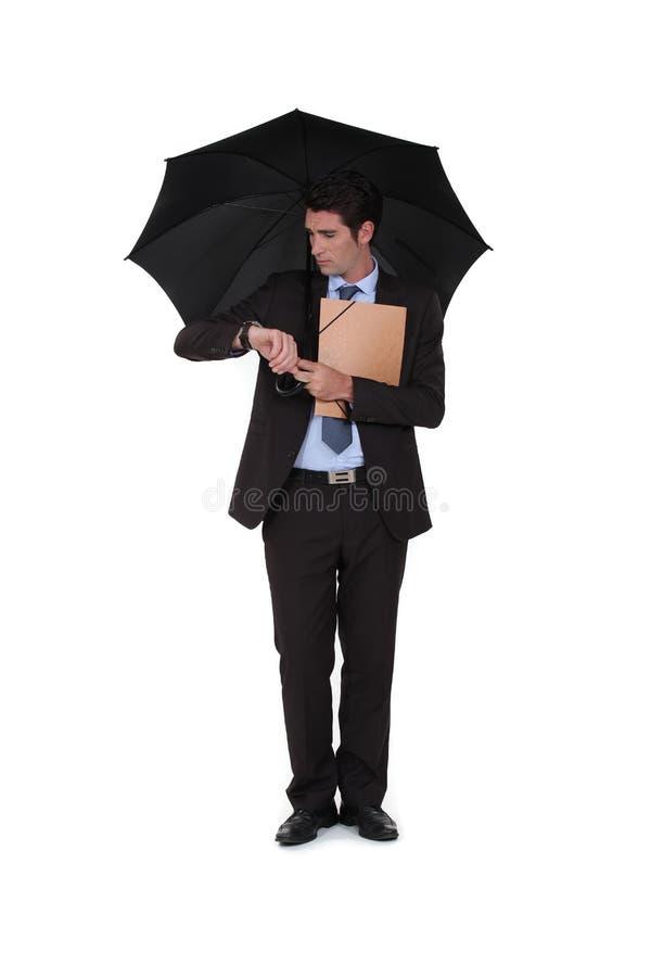 A businessman under an umbrella stock photos