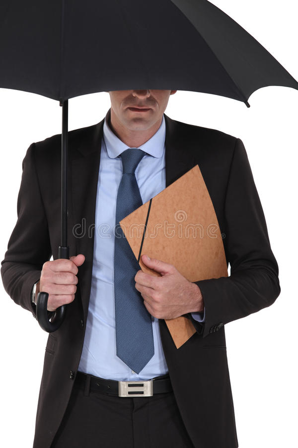 Businessman under an umbrella stock photo