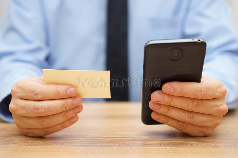 Businessman use contact information from business card to cont royalty free stock photo