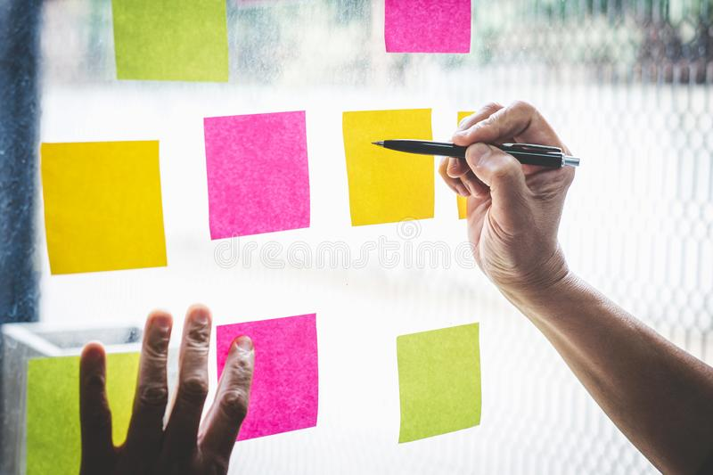Businessman use post it notes to planning idea and business marketing strategy, Sticky note on glass wall.  royalty free stock photo
