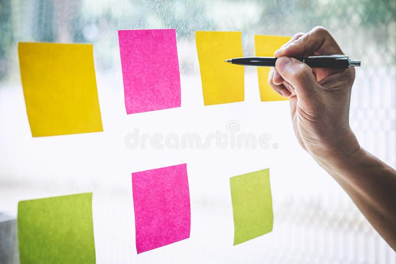 Businessman use post it notes to planning idea and business marketing strategy, Sticky note on glass wall royalty free stock photos